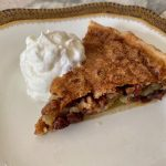 A piece of Osgood Pie on a white plate with whipped cream on the side and raisins adn pecans showing in the filling