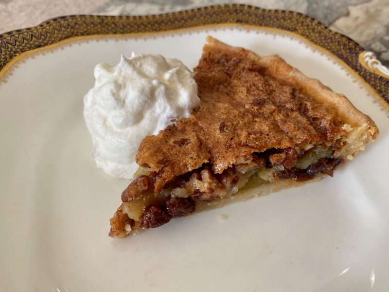 piece of Osgood Pie, creamy filling with pecans and raisins, on white plate with gold trim and whipped cream on the side