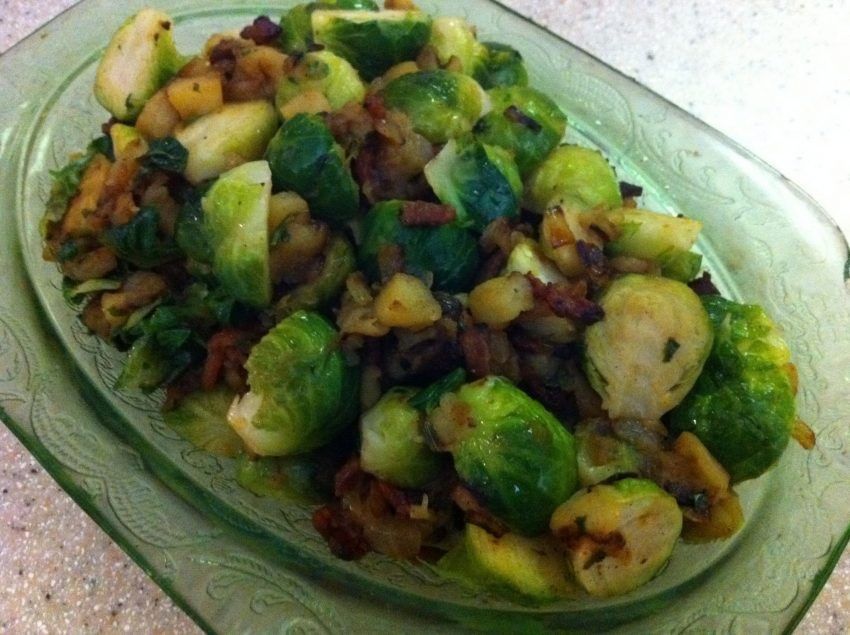 Brussels sprouts halved and cooked with bacon and apples in green depression glass bowl