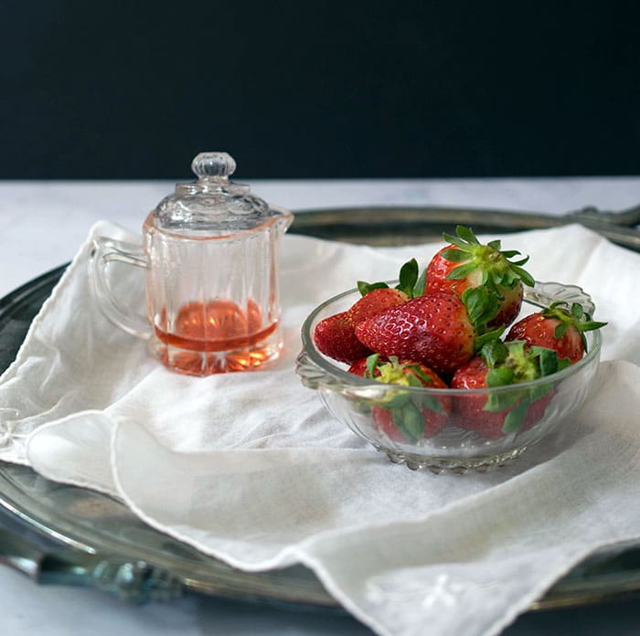 Shrub in petite glass pitcher with top, next to small glass bowl of whole berries, on white linene , on a tray on a marble table with black background in the distance