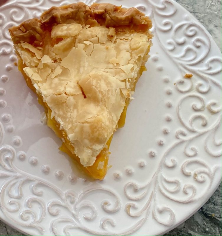 One piece of mango pie, double crust, on a white dessert plate with raised designs