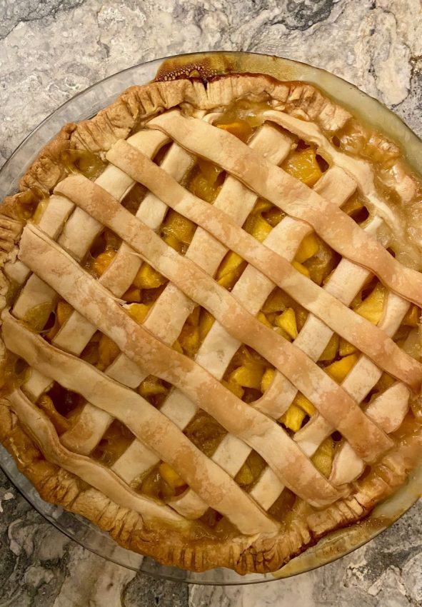 Fresh mango pie from above, with a quick-lattice top crust and and juicy filling peeking through, on a marble countertop