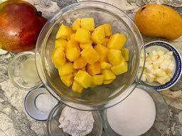 Big glass bowl of peeled mango chunks, surrounded by small containers of the recipe's ingredients: lemon juice; salt; flour, sugar, butter, and two whole mangoes, all on a marble surface